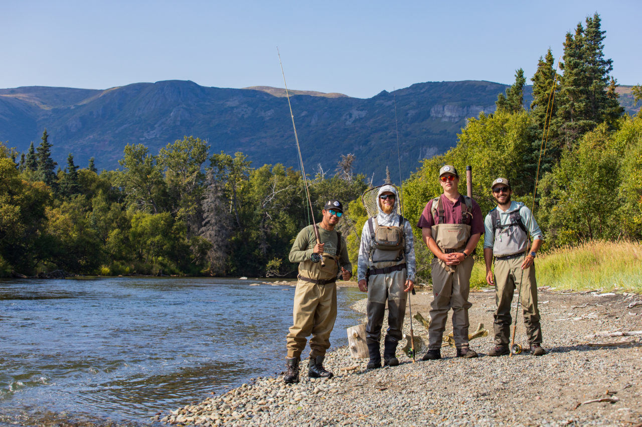 A group of four anglers stand in a line to get their picture taken before starting the Alaskan fishing season.
